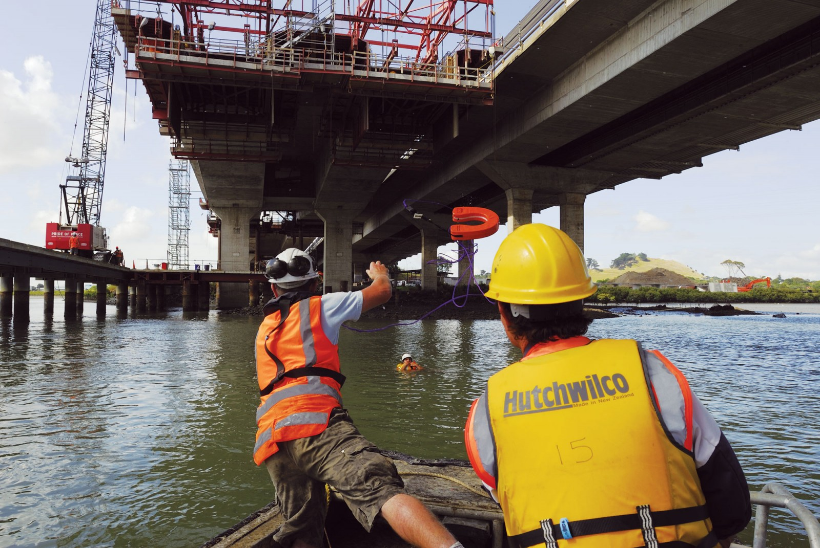 "Pier foreman Chris Murphy throws a line to a waterlogged Johny Hope during a simulated rescue beneath the Mangere Bridge project. The monthly safety drill usually goes unannounced until a horn sounds three blasts, making it more authentic for workers. Candidates to be rescued are arbitrarily selected from the crew, says Murphy, ""based on who pissed me off the most that month""."
