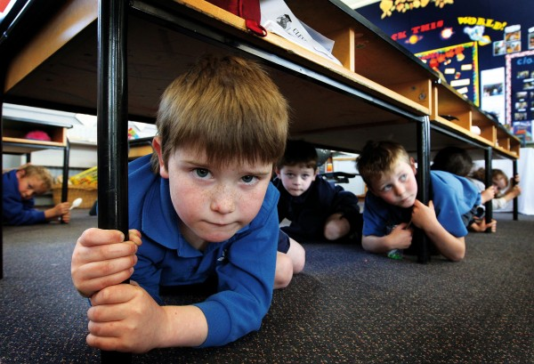 Amidst the aftershocks, Lachlan Botting and his Belfast School classmates perform safety drills on their first day back at school.