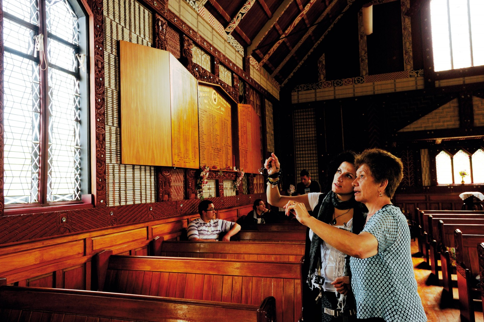 Paniora Maori Josephine Kalan explains to her Spanish cousin Monica Garcia the significance of the carvings and tukutuku panels in St Mary's church, Tikitiki, which is considered by Ngati Porou to be their cathedral.