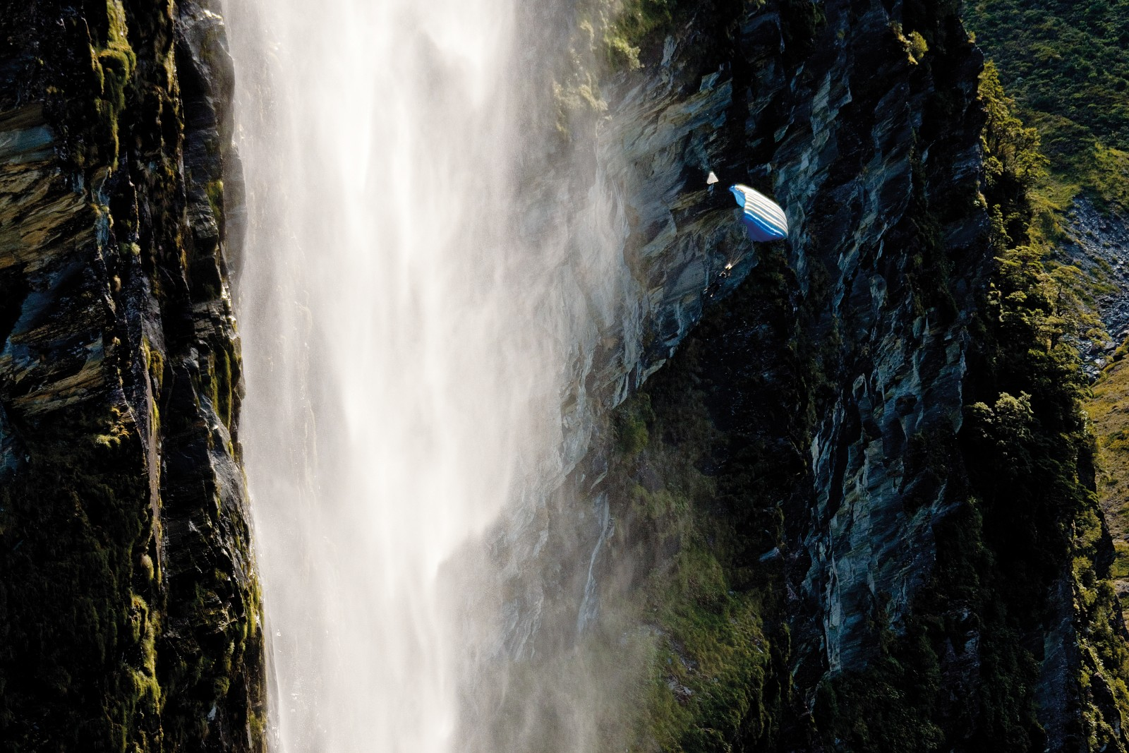 Craig Taylor deploys his canopy beneath the falls of The One in Mount Aspiring National Park, and sails to safety in a shroud of mist. Like many BASE jumpers, Taylor has had his share of injuries and close calls, but moments like this keep him coming back to the sport.