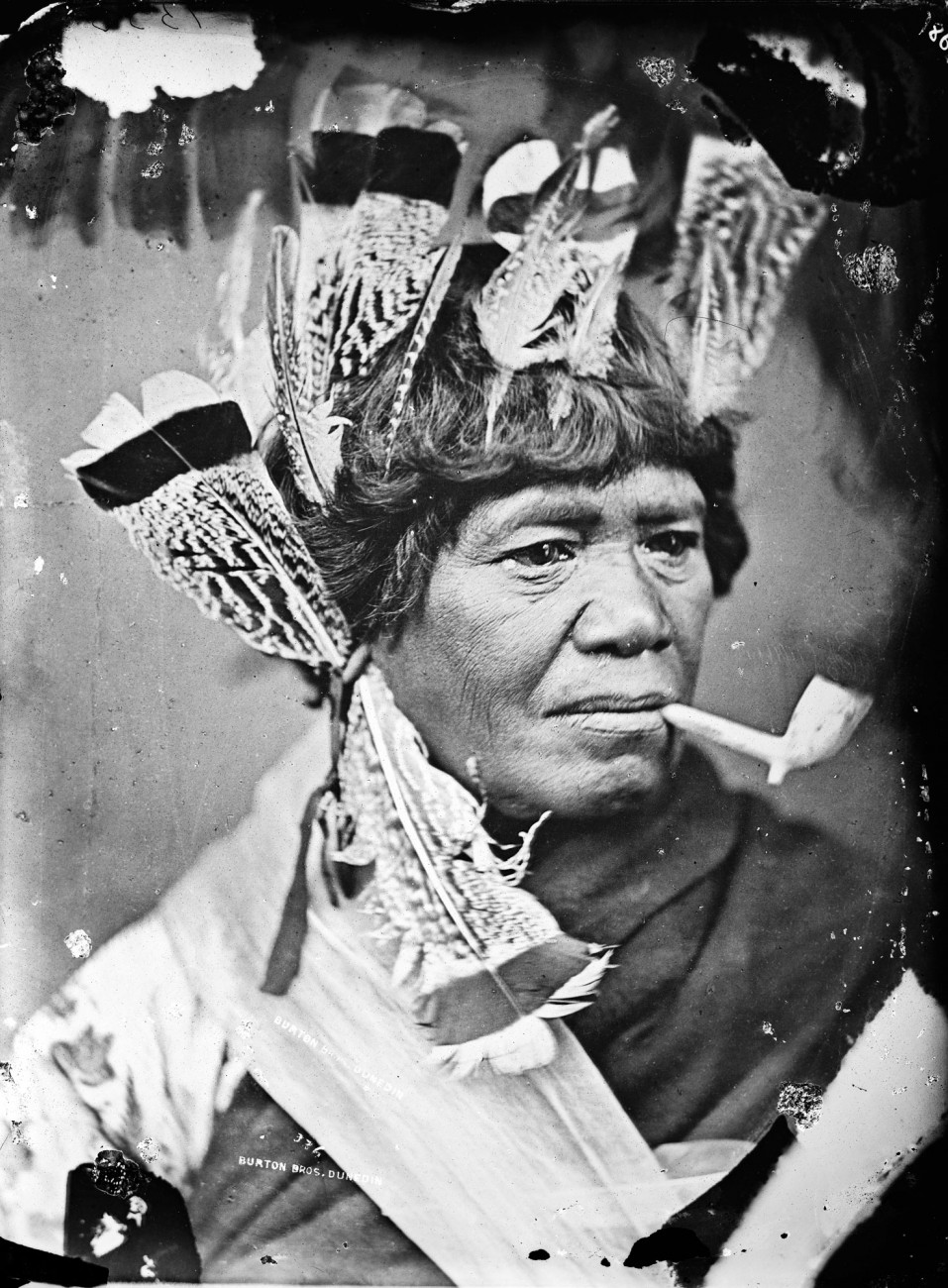 Many of McGarrigle's Maori portraits bear an unmistakable resemblance to contemporary photographs of Native Americans yet, despite trading as the American Photographic Company, there is no evidence that he ever visited that country. It was common at that time for photographers to keep a wardrobe of clothes and accessories for dressing their subjects. But a hallmark of McGarrigle's Maori images is that, however much they may deviate at times from historical accuracy, they never seem forced or imposed. As with many of his portraits, this image carries the name stamp of photographer Alfred Burton, who purchased a collection of negatives when McGarrigle moved to Australia.