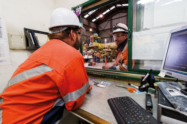Mobile equipment supervisor Mike Scurr discusses excavator maintenance with technician Andrew Cooper in one of the OceanaGold workshops at Macraes mine.