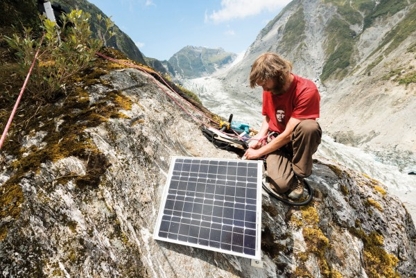 Brian Anderson perches on a ledge high above the Fox Glacier to reposition a solar panel that powers a monitoring camera. The camera takes a picture every hour, recording the flow of the glacier, and events such as crevasse formation and ice collapses as the ice moves down the valley. The Fox Glacier has been rapidly shrinking over the past century and a half, just like the Franz Josef where records of the terminal position date back to 1860. They show a long retreat, marked with a number of small advances due to periodic high snowfall on the Main Divide.