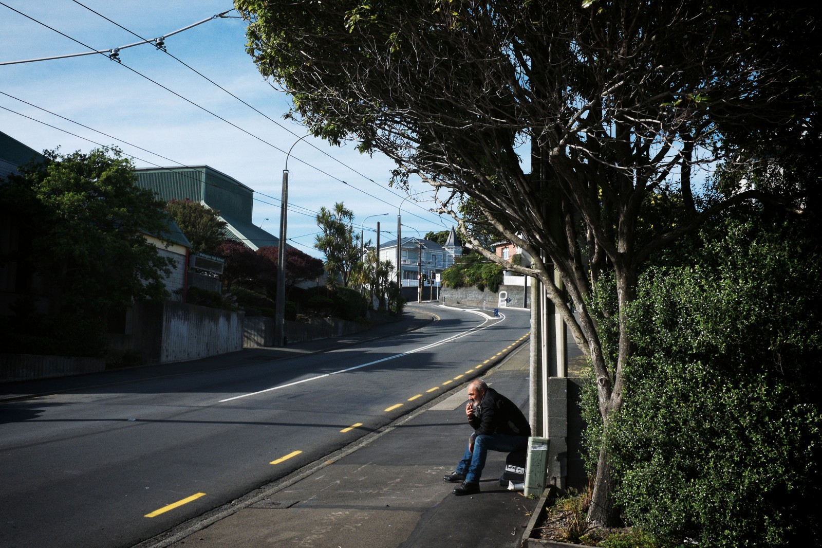 'Ari', a man who has experienced homelessness for over a decade, sits on a bench outside the Wellington night shelter on upper Taranaki Street. The night shelter provides beds for 45 men, many of whom, like 'Ari', are cycling through different types of sub-standard housing. Wellington Council has recently provided funding for a social worker to help guests engage with health and other services, but the shelter lacks the funding to assist everyone who comes through its doors.