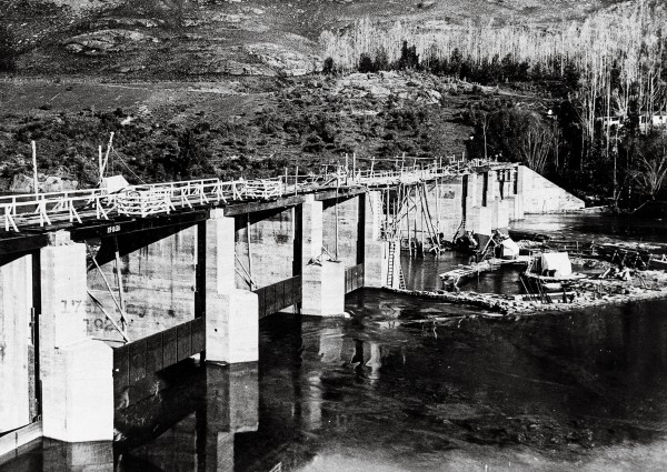 "In Anno Domini 2000, Vogel imagined the Kawarau River dammed to reveal vast amounts of gold in its now dry bed. In 1924, a very similar scheme was actually initiated, and this photograph, taken in the winter of1926, shows work in progress. A prospectus issued in association with the scheme quoted Vogel's book to bolster a claim that there were ""tons of gold in the crevices and among the rocks of the rough bottom and rocky sides"" of the river. In fact, the river bed proved largely bereft of precious metal."