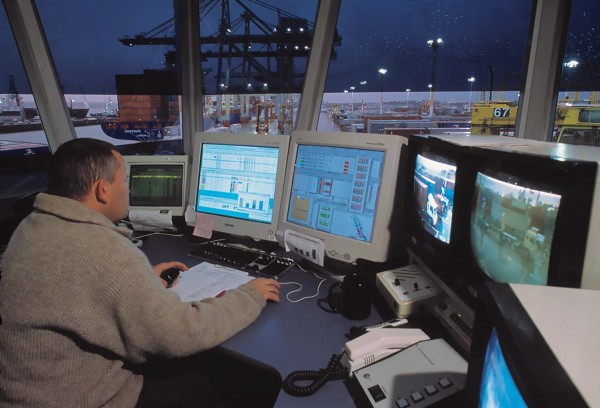 Every loaded container is tracked by computer from despatch point to destination—including its whereabouts in a ship's hold and its progress across the wharves. Staff such as Kevin McCormack, in the Ports of Auckland control room, direct container-crane and straddle-carrier operators in their every movement, while computers figure out the most efficient way of moving the tide of steel boxes.