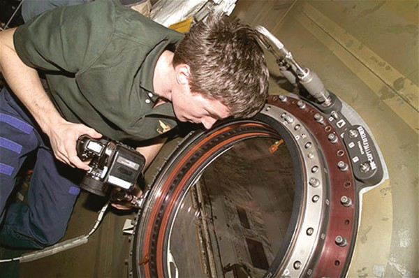 Russian cosmonaut Sergei Krikalev savours the view from the new optical window on the US Laboratory Destiny.