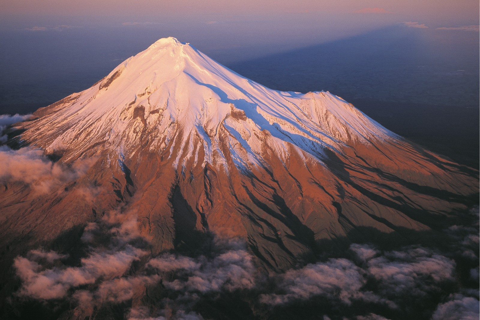 Beautiful but not benign, Mt Taranaki experiences a miserable climate. Rainfall is 7.5 m a year, and the average wind speed on top is 40 km/h. Alpine herbs extend up to about 1700 m, and between 1400 m and 1700 m is a band of tussock. Scrub and shrubland cover the slopes between the bottom of the tussock and the tree line at 1100 m. The last eruption was about 250 years ago, and it is considered unlikely the mountain has forsaken its tantrums permanently.