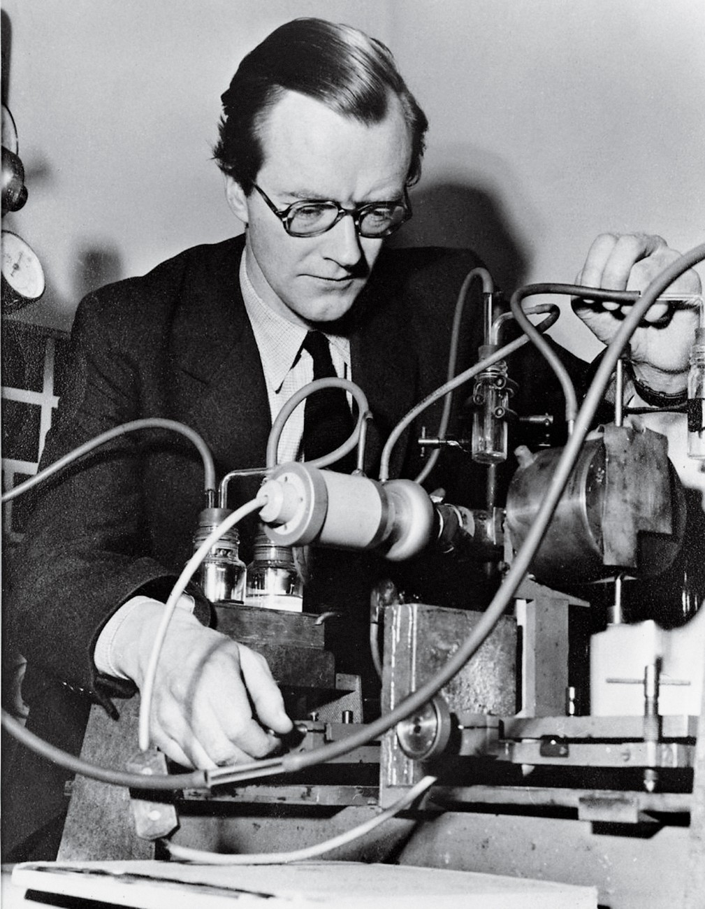 Here Wilkins adjusts an X-ray camera at King's College, London, in the mid 1950s. A piece of lead behind the cylindrical camera absorbs most X-rays while a few are scattered by the sample of DNA fibre—in a container in front of the camera—to produce an image on film. Exposures of five hours were needed to obtain such an image.