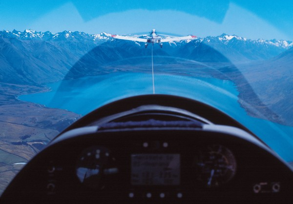 Getting a glider airborne usually requires the help of a tow plane. As a Piper Pawny hauls its unpowered charge over Lake Ohau towards the Southern Alps, the clear peaks and cloudless sky betoken little in the way of wind and therefore poor gliding conditions.