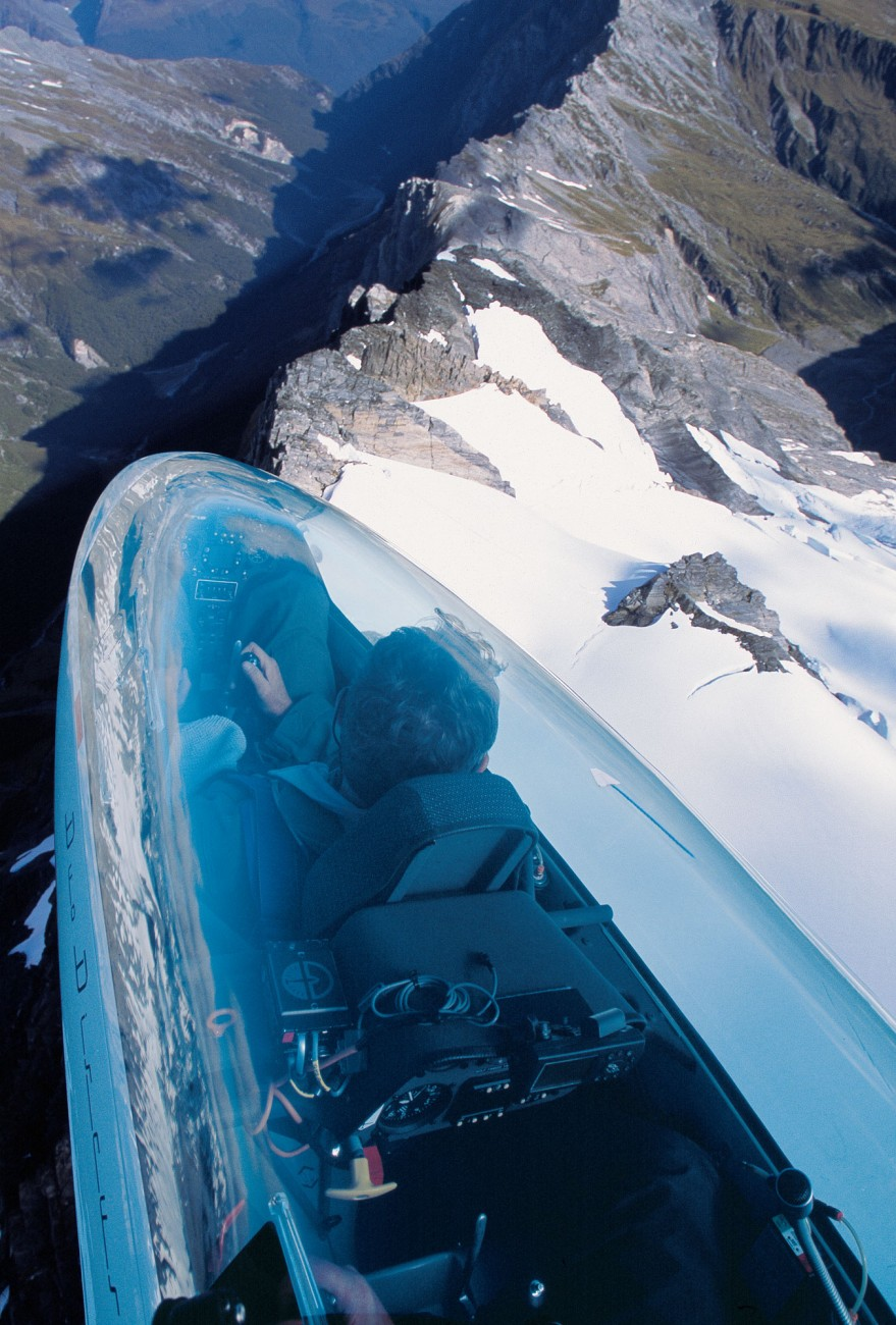 Instructor Gavin Wills banks to starboard as he circles in a column of ridge lift to gain altitude. Straying over the deep valley would take the glider into a downward eddy, with disastrous consequences. From a higher altitude, however—nearer 3000 ft (910 m)—it will be possible to dive across the liftless zone to the windward side of a neighbouring ridge, there to begin climbing again.