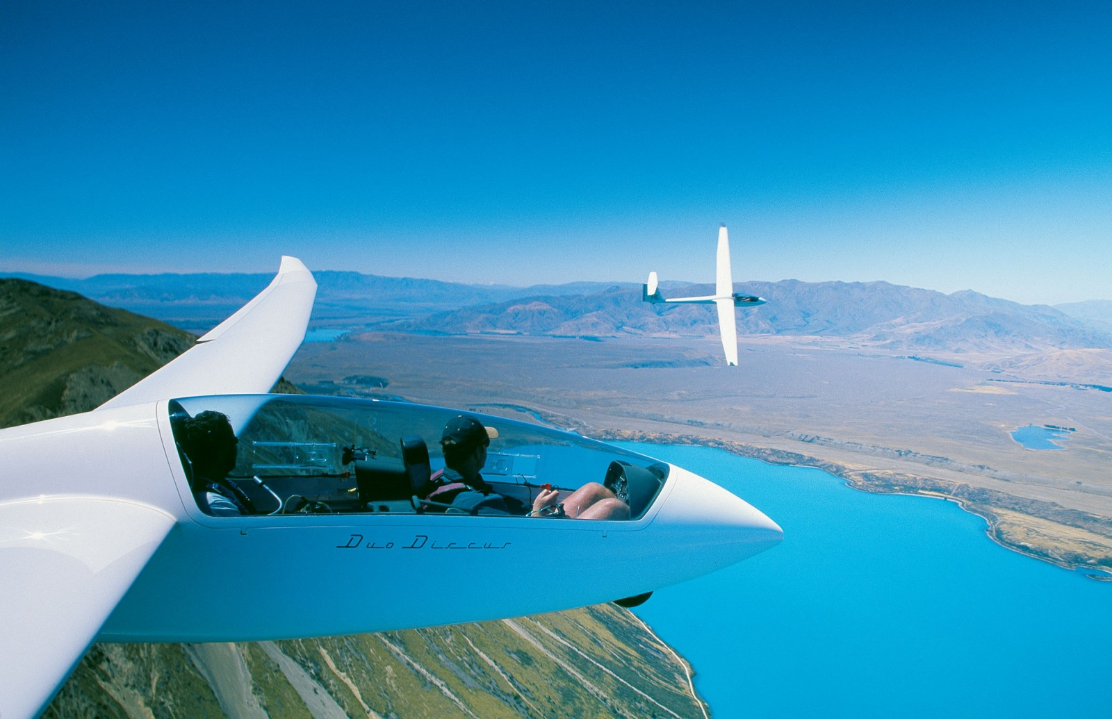 """You have control,"" intones Luke Roberts, instructor, from the back seat (right). In front, author Marty Taylor enjoys a spot of Mackenzie Country magic ashe pilots the Duo Discus over the slopes above Lake Ohau. Beyond the accompanying glider the Benmore Range bestrides the horizon, falling towards Lake Ruataniwha, at Twizel, under the Duo's port wing."