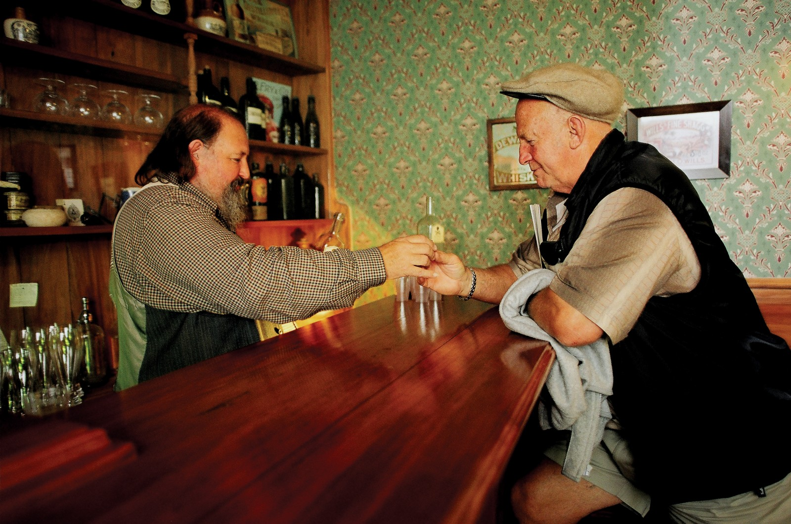 "A mock barman in a mock bar: folk singer Phil Garland pours the ""last drink"" inside the Hokonui visitor centre during the Hokonui Moonshiner's Festival, held one weekend each February."
