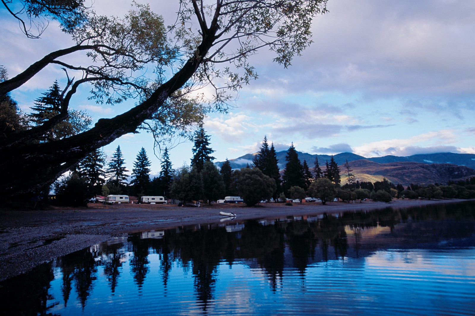 """Glendu Bay, beside Lake Wanaka, is a large and very popular camp. Set up on land gifted by a local farmer in the 1930s, it holds close to 2000 visitors at the height of summer. Chris Illingworth, the lease of the operation, says that 90 per cent of campers return year after year and a few have been coming for 60 years. """"It's not just a camp, but also a busy store. It's really a small town. And in addition to the people, tents and vehicles, there are 300-400 boats! We have a staff of 18 at the peak of the season."""""""