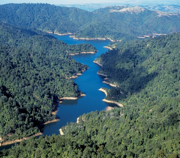 The Hunua Ranges reach a height of 688 metres and attract about 50 per cent more rain than surrounding areas. Steep valleys make for long narrow lakes behind the four large dams, as can be seen in this view looking south-east over the Mangatangi Reservoir towards Miranda.