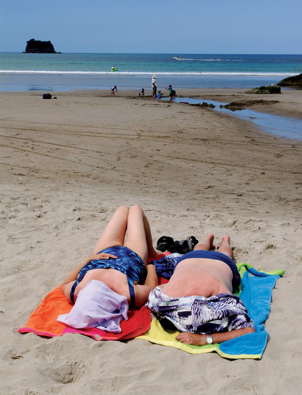 A Sunday afternoon siesta on an uncrowded beach suffices for some, while children play in tidal pools near the Otahu Estuary.