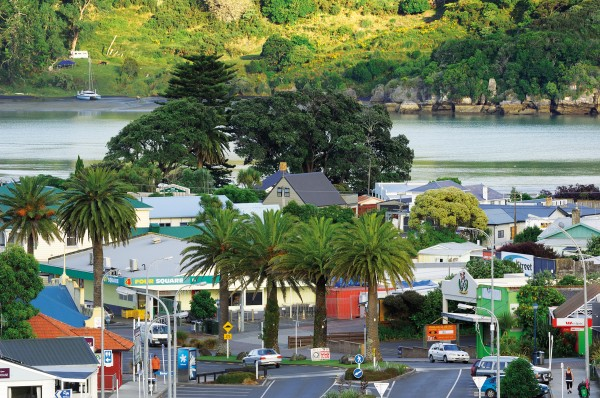 Visitors to Raglan are treated to a visita of Raglan's palm-lined mainstreet, with Whaingaroa Harbour beyond, from a rise on state highway 23.