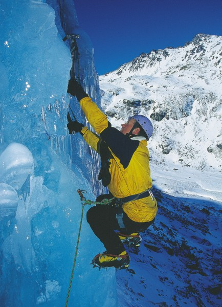 "The author demonstrates a classic ice-climbing position, the ""monkey hang."" Using crampons, the climber works himself into a crouch. Then, in a sudden movement, stands up to place the ice axe in a new position-typically above an obstacle or patch of bad ice. While in the crouch, the climber's total weight is supported by the arms."