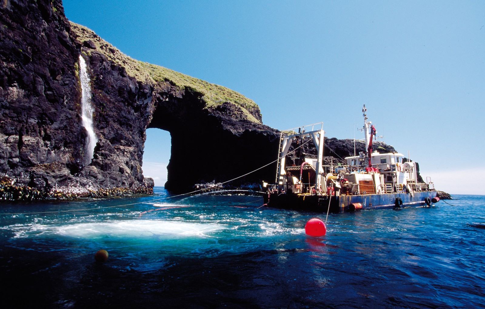 The Seawatch on station. Due to its exposure to violent subantarctic westerly weather systems, diving on the Rifleman wreck site was possible on only one day in four. The site, about halfway down Auckland Island's rugged west coast, was a mere notch in vertical cliffs, connecting to the sea through an archway (pictured) and a narrow entrance. While some aspects of the site corresponded with survivors' descriptions of the General Grant wreck site—there was a cave within the small cove—none of them mentioned an archway or a waterfall.