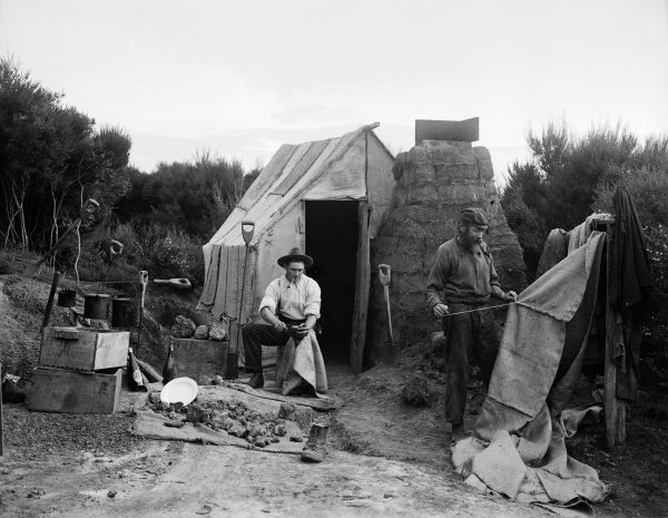 Sod and sacking huts were typical gumdigger shelters right Lip until the 1930s. Here one digger sell's sacks for roof and walls while another scrapes gum. Note the billies hanging on a gum spear over an open fireplace.