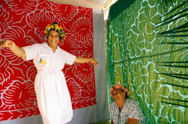 Skilled hands make pandanus products in a Mauke craft collective (top) while two women show off their floral-print tivaevae (decorative cloths) at a craft display (bottom).