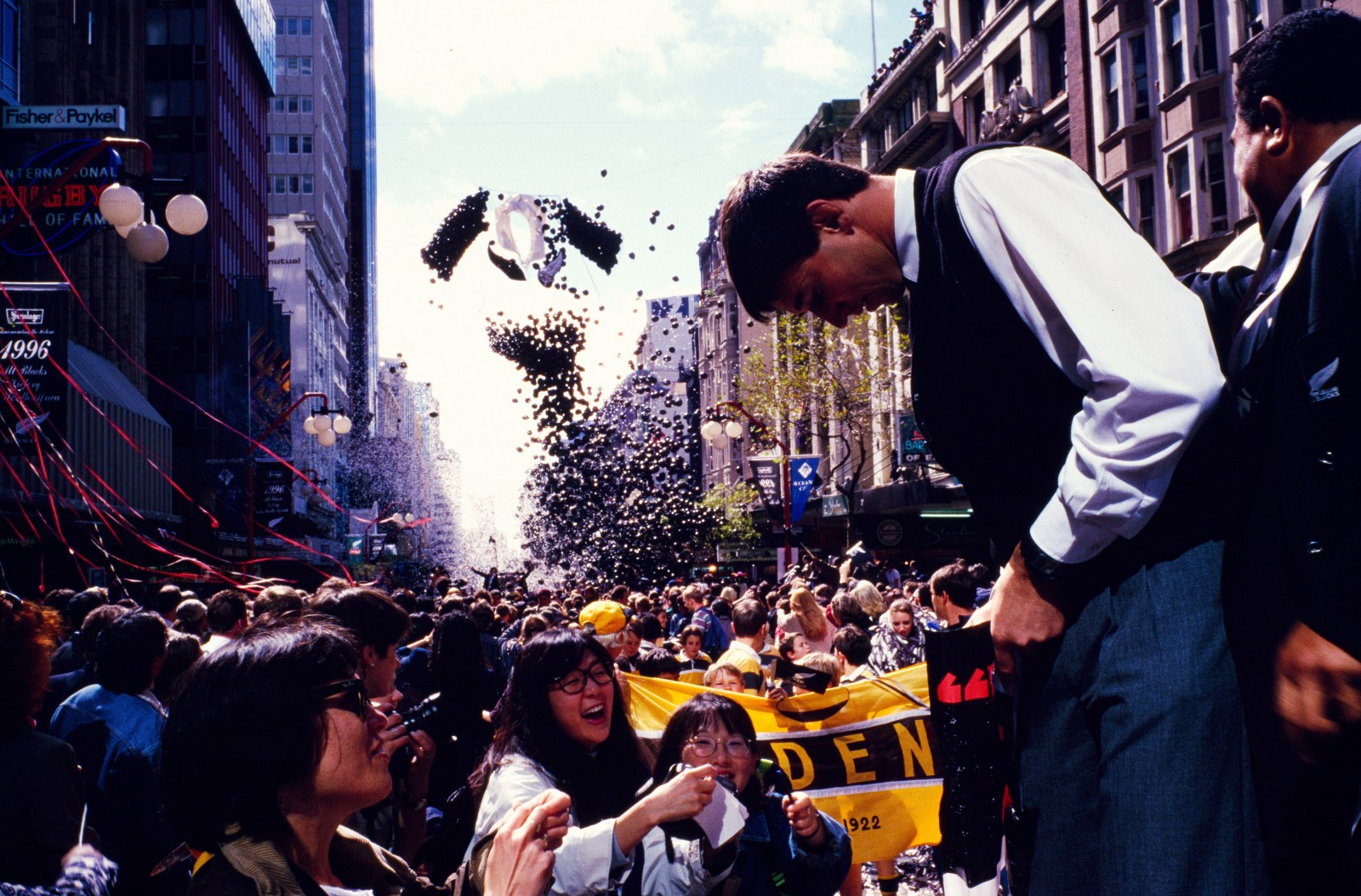 "Dubbed ""The Incomparables,"" the 1996 All Blacks returning from the first ever test series win in South Africa were feted by thousands of supporters on the streets of Auckland. Lock forward Ian Jones signs for a fan as a huge All Black jersey made of balloons is freed."