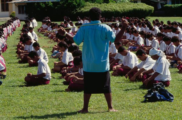 A big stick helps ensure that the pupils of Maluafou College stay in line as they practise a s'asa'a (slap dance) for Western Samoa's Independence Day celebrations. Vigorous corporal punishment is a fact of life for Western Samoan children in school, church and home.