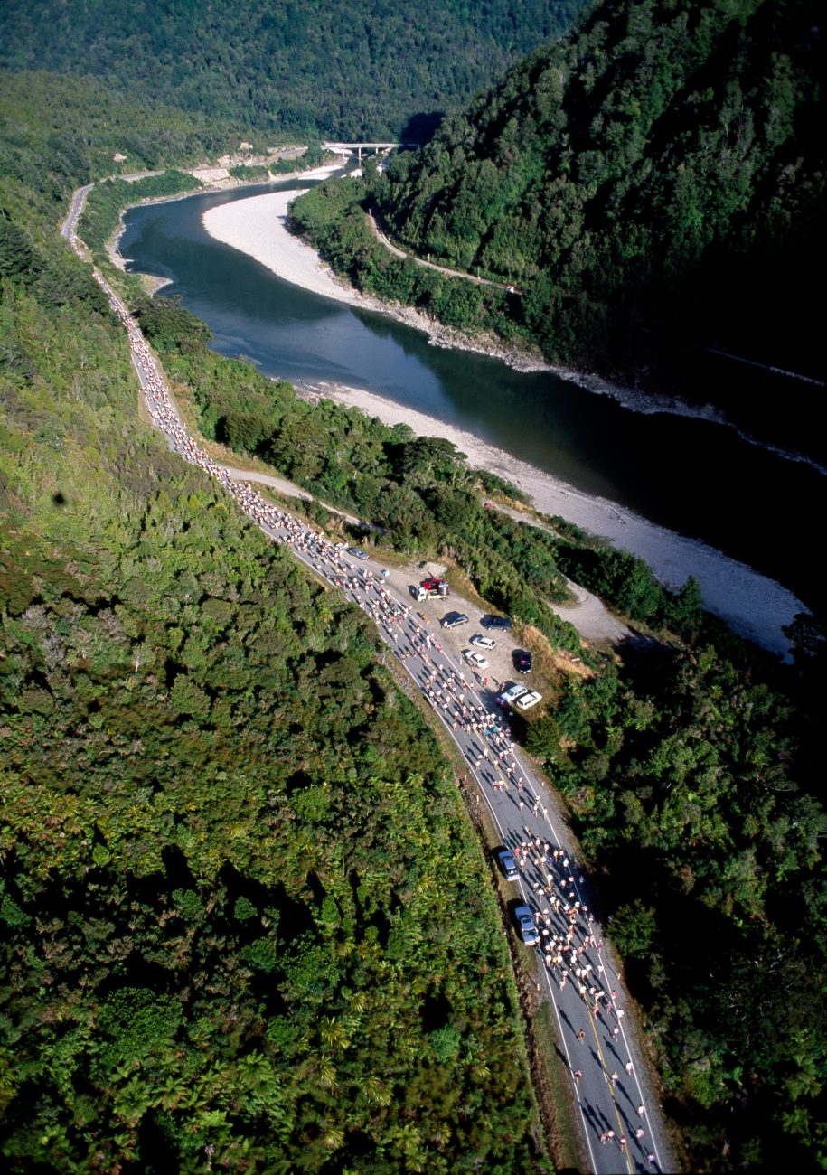 Fourteen hundred runners pound State Highway 6 beside the temptingly cool waters of the river in the 15th Annual Buller Gorge Marathon, The broken mountains of the region confine the highway—the only road connecting Nelson and Marlborough with the West Coast—to the environs of the river for 150 kilometres, producing one of the most scenic drives in the country.