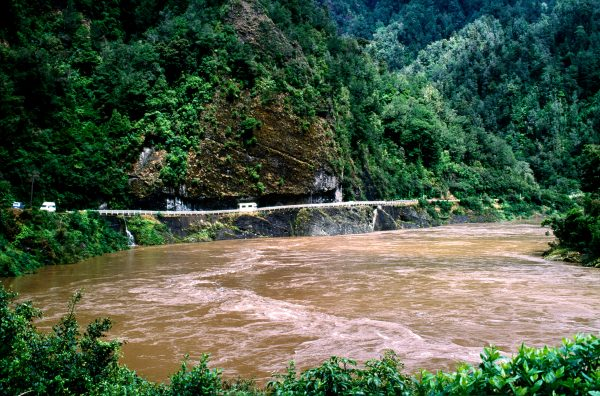 Laden with soil from thousands of square kilometres of wild backcountry, the flooded Buller surges past Hawks Crag, a rock precipice into which a one-lane-wide slot for the road has been incised. The river's normal level is 15 metres below the road, but in high flood the water has risen above the railing.