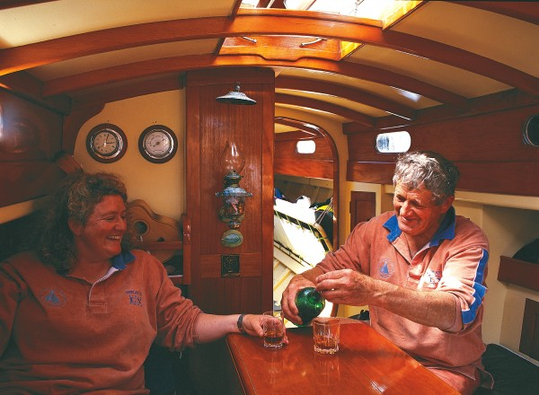 Despite kauri's legendary resilience, boats made of this premier timber require countless hours of maintenance to ward off the ravages of sun, salt water and sea air. On Waiheke Island, Ben Robertson and Brydee Rood sand the Bailey-built Matua, launched in 1900 and later rebuilt as a gaff yawl, preparatory to giving her a fresh lick of paint. In Spray II's varnished saloon (below), Johhn Duder enjoys the traditional sailor's tot with his daughter, Lisa.