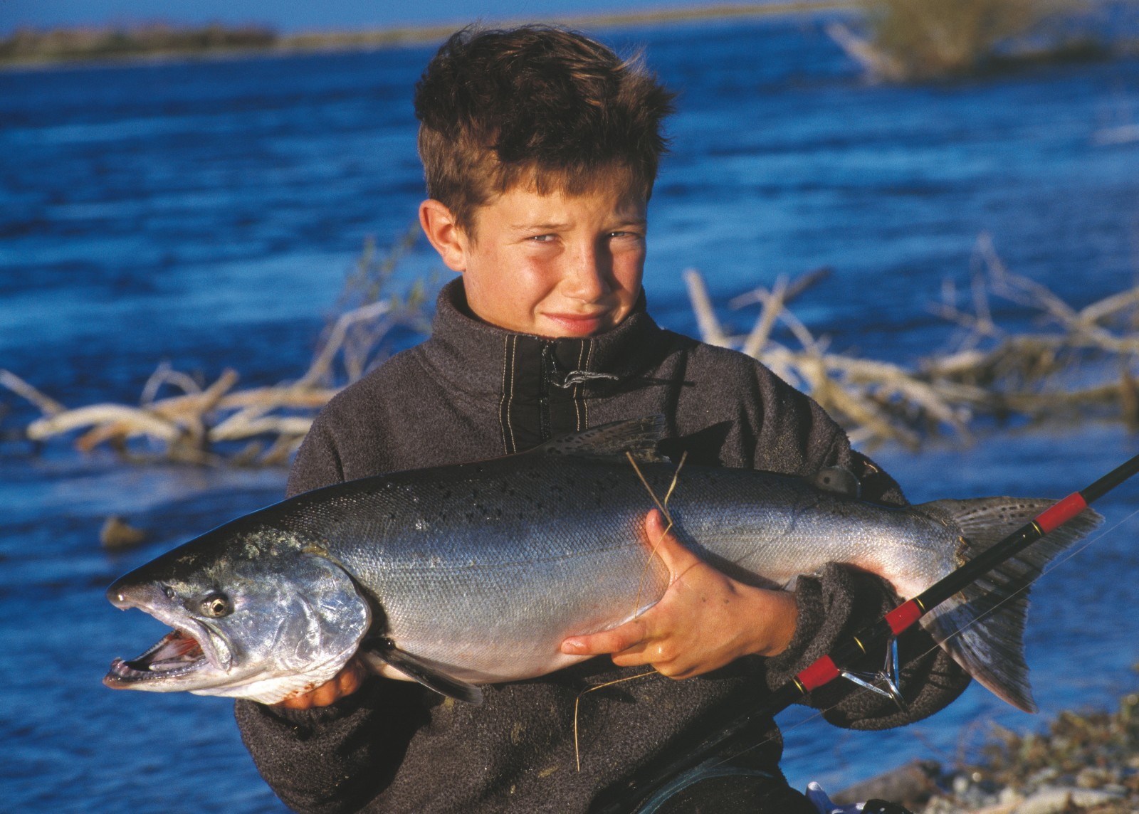 Historically prized for its eel, whitebait, lamprey and mullet fisheries, the Waitaki is now a Mecca for trout and salmon anglers. The author's son Jeremy, here displaying a 6 kg salmon he landed from the Waitaki, caught his first trout at the age of three. The river is one of relatively few in the country to host thriving populations of both trout and salmon.