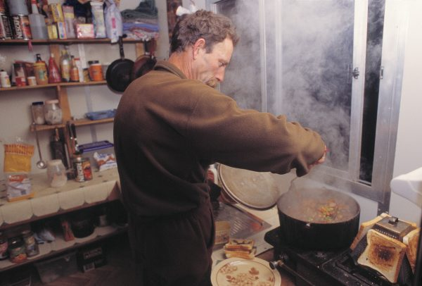 Manager Charles Feast cooks a hot meal before heading out for a night's possum shooting on Tarawera's slopes.