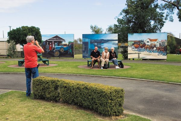 Visitors pose in front of murals depicting aspects of the town's history. Foxton is developing its past and adding a few embellisments—such as the windmill—to increase the number of visitors, a key, it believes, to a prosperous future.