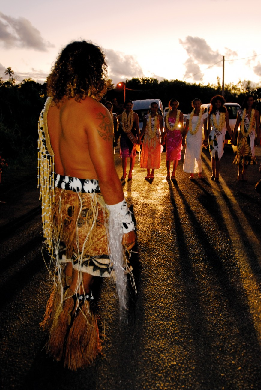 As part of the Tiare festival programme, contestants in the Miss Tiare beauty pageant travel the 32 km circuit around the island of Rarotonga to be introduced to each of the oire, villages. As twilight descends over Black Rock on the edge of Arorangi, contestants are greeted with a traditional warrior welcome by members of the Puaikura district.