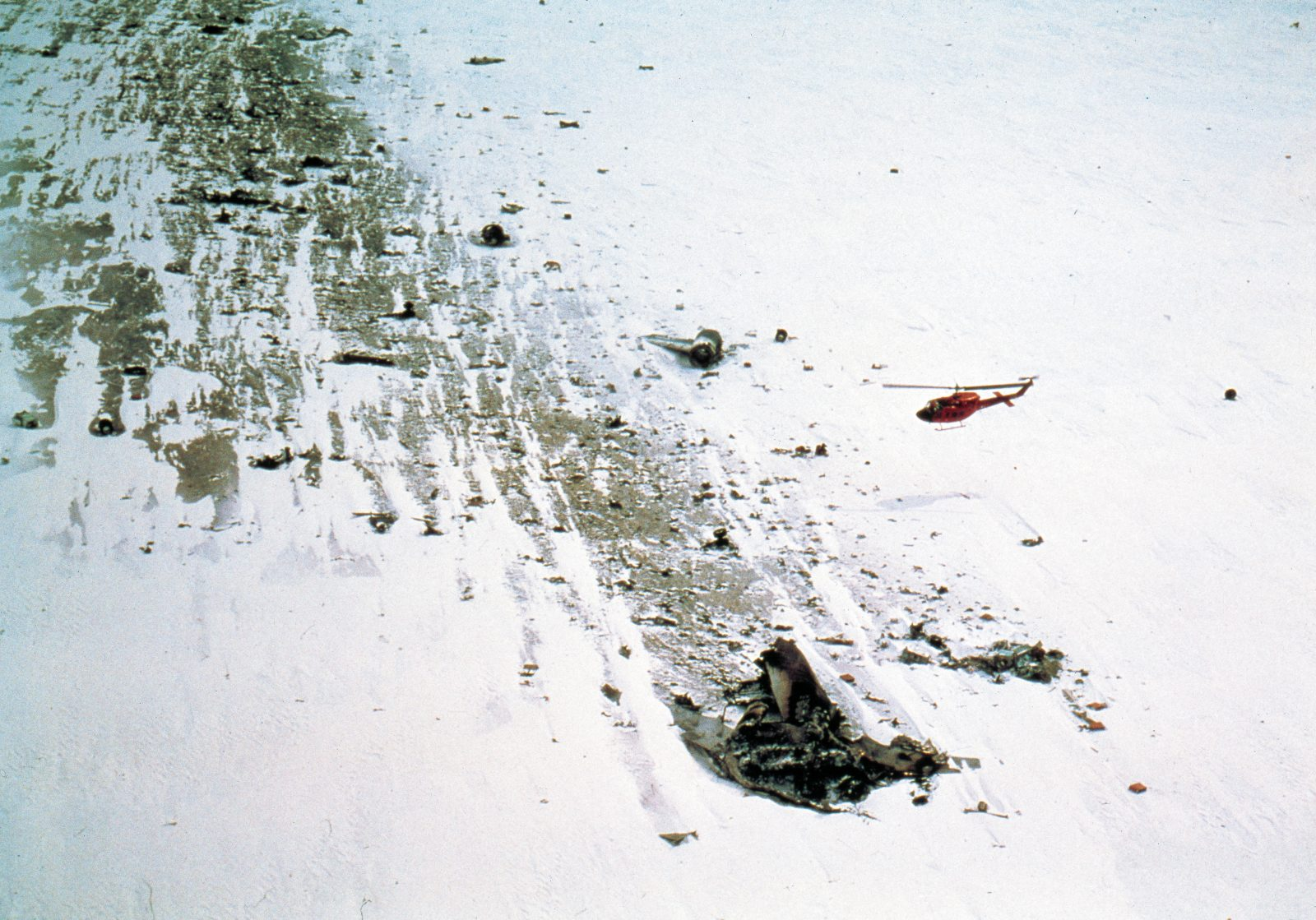 A US Navy helicopter flies over the wreckage soon after its discovery. The crash point is at the upper left. The force of the impact, which rendered much of the wide-bodied DC10 unrecognisable, opened crevasses on the sloping ground, adding to the dangers for the recovery team.