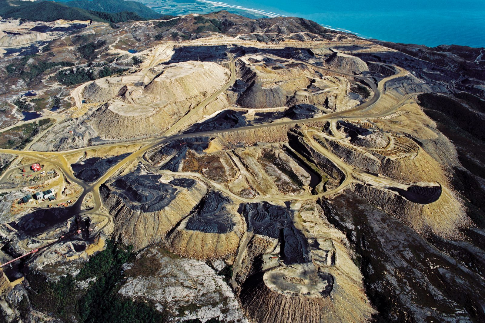 Two million tonnes of bituminous coal are mined each year from Stockton Plateau, New Zealand's largest opencast mine. Most of the coal is exported for steelmaking—as is coal from Denniston, which lies beyond the top left corner of this photograph, taken in 1998. The peaks on the ridgeline at top centre are part of the Mt Augustus massif, where a remnant population of the eponymous land snail was discovered 20 years later. The entire ridge has now been flattened.