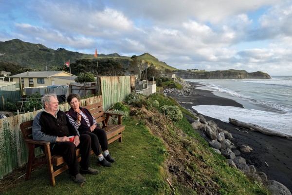 "Fifty years ago, there were houses and a road in front of Bev and Ray Christiansen's place at Mokau, on the Taranaki coast. The sea has clawed back that land, and high seas now wash up to the Christiansens' fence. Residents banded together to protect the dune edge with boulders, but the council has forbidden any further protection work. ""We're probably sitting on a time bomb,"" says Bev."